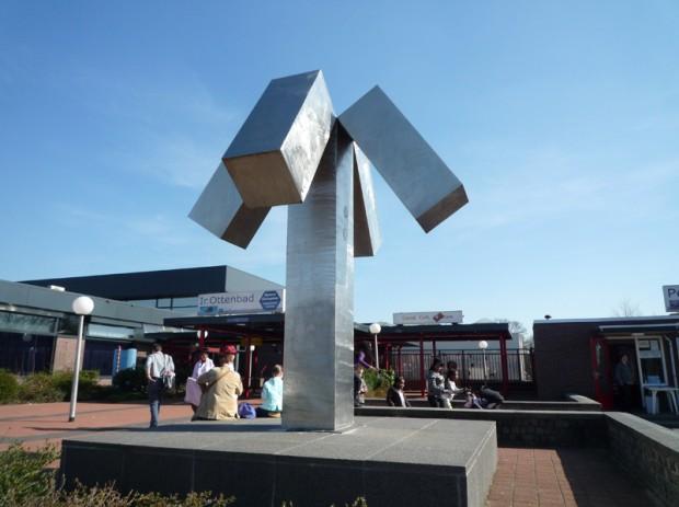 1975 plaatsing in Eindhoven. (ontwerp 1971), Jan Goossen, East Jesus County Revisited, roestvrij staal . Ir. Ottenbad Eindhoven. Ontwerp 1970. Zuil 370x80, kruisstuk 200x200x100. foto Yvette Lardinois
